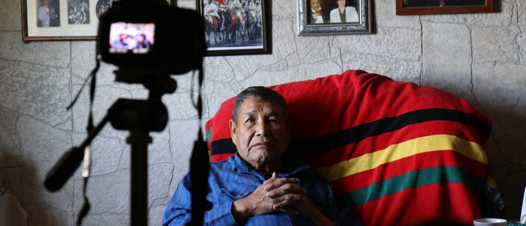 Piikani man at home being filmed