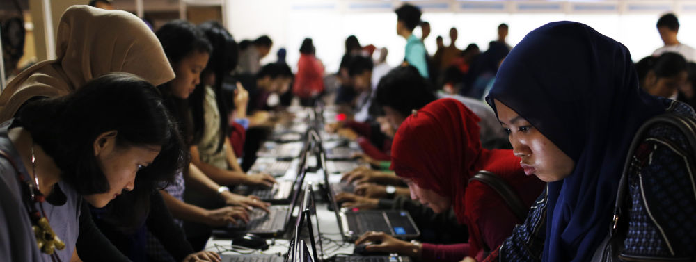 Indonesian youths fill out job application forms on laptops provided by the organizers at Kompas Karier Fair in Jakarta