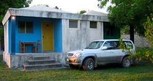 A white truck in front of a single story house in Haiti