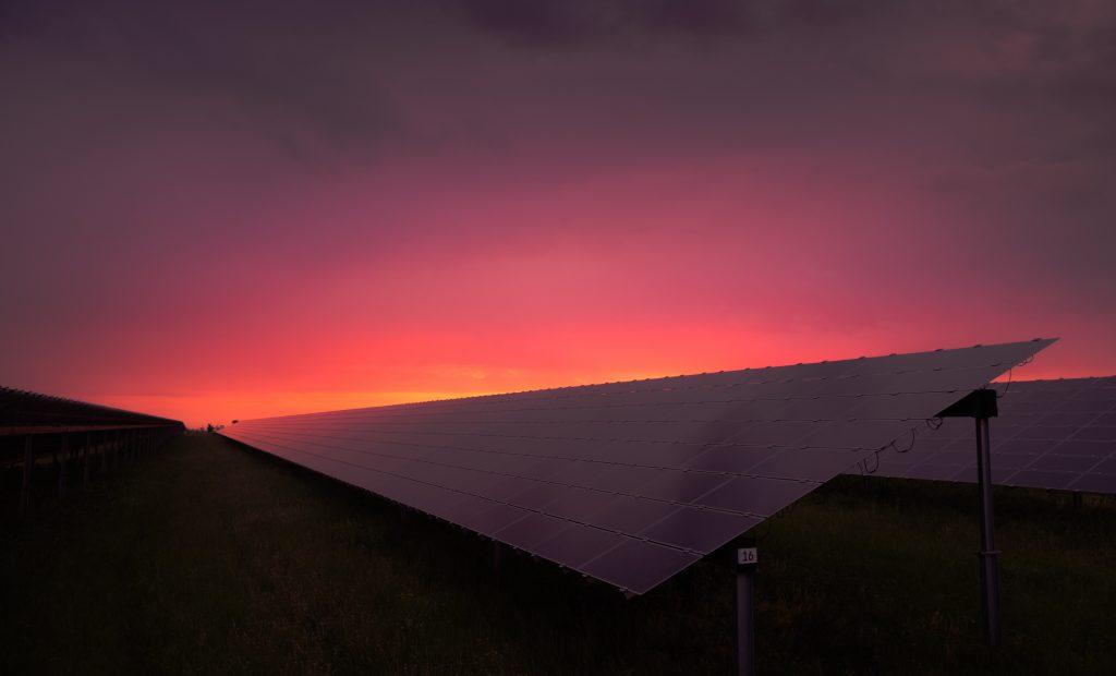 Red sunset over a solar farm