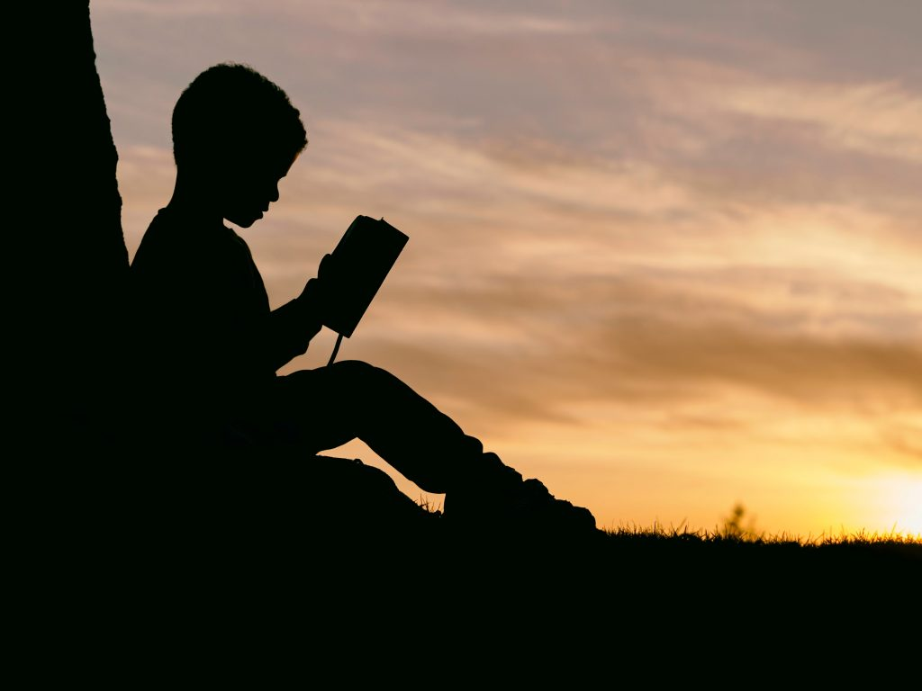 Silhouette of a boy reading in front of a sunset