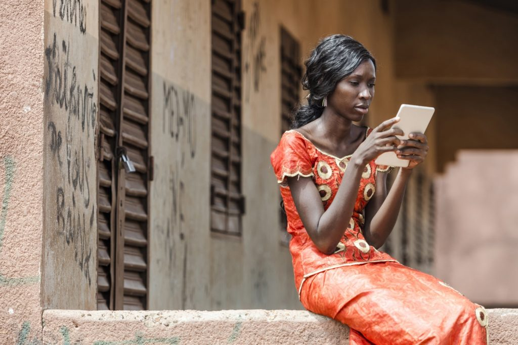Young woman in orange dress uses a tablet computer