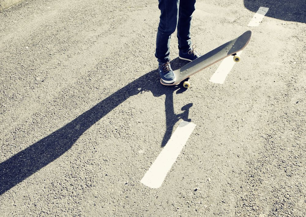 A person standing on a skateboard on a road