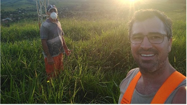 Two Brazilian community network engineers standing in a wide grassy field in front of an antenna