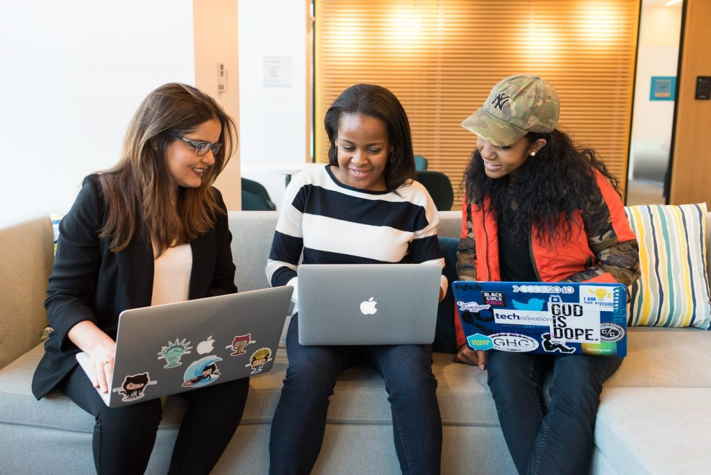 Three women working together on laptops