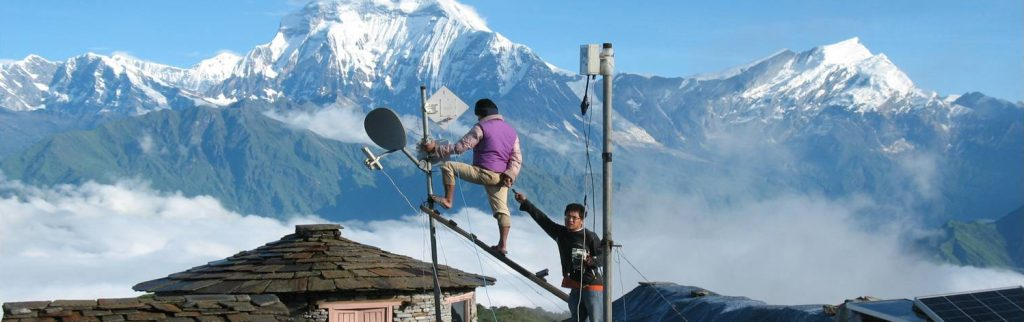 Two men fitting antennae on top of a room in front of the Himalaya mountains in Nepal